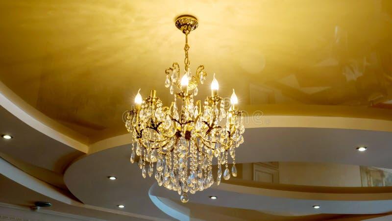 有垂悬在一块豪华天花板的蜡烛的富有的美丽的金黄枝形吊灯 库存图片