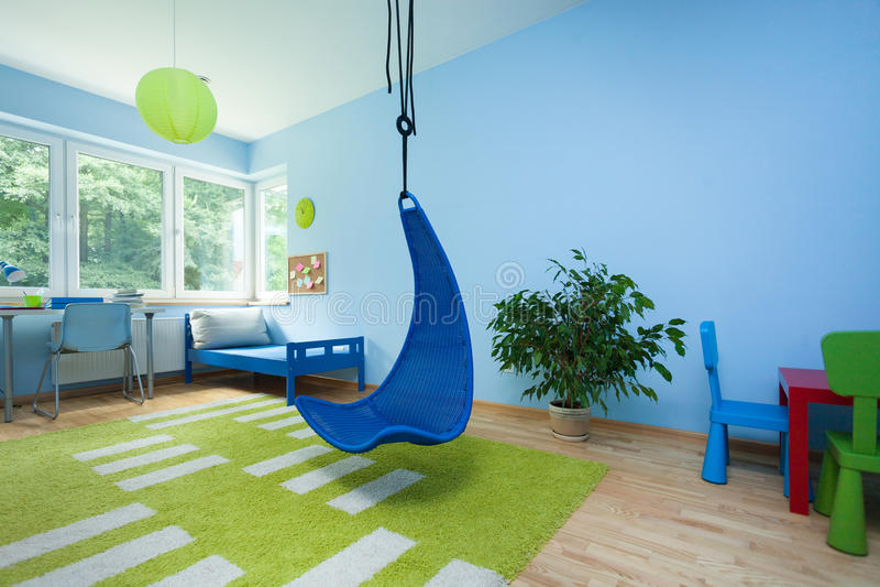 有垂悬的椅子的儿童居室 库存照片