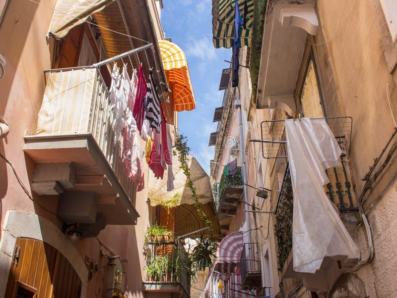 有垂悬的狭窄的街道在阳台穿衣在意大利,巴里的南部 在阳台的干燥洗衣店 意大利南部的建筑学 免版税库存图片