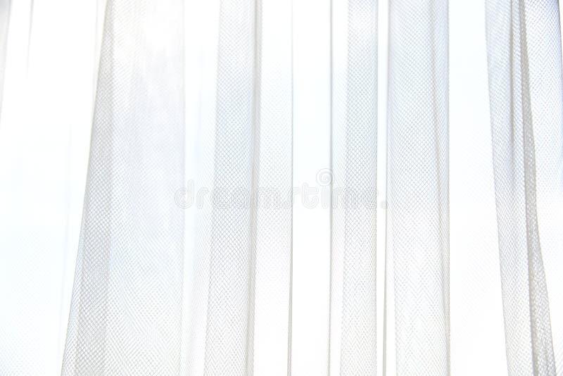 有垂直的折叠的白色薄纱帷幕 与轻的帷幕的窗口 软的纺织品纹理 光和阴影摘要 库存照片