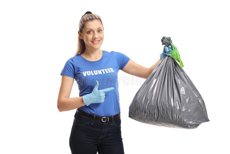 有垃圾袋的妇女志愿者指向它的 库存照片