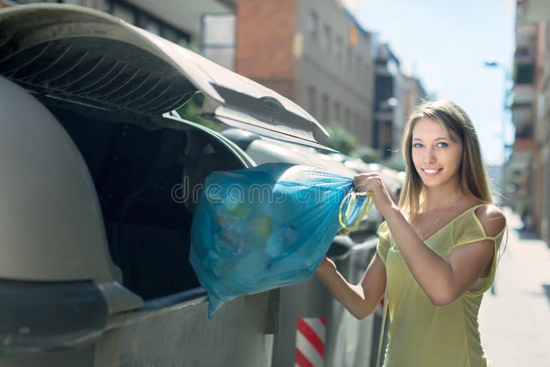 有垃圾袋的妇女临近垃圾桶 免版税图库摄影