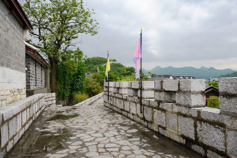 有城垛和旗子的石墙在多云的雨以后以后 免版税库存照片