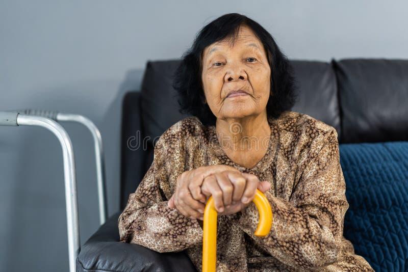有基于和坐长沙发的藤茎的资深妇女 免版税库存照片