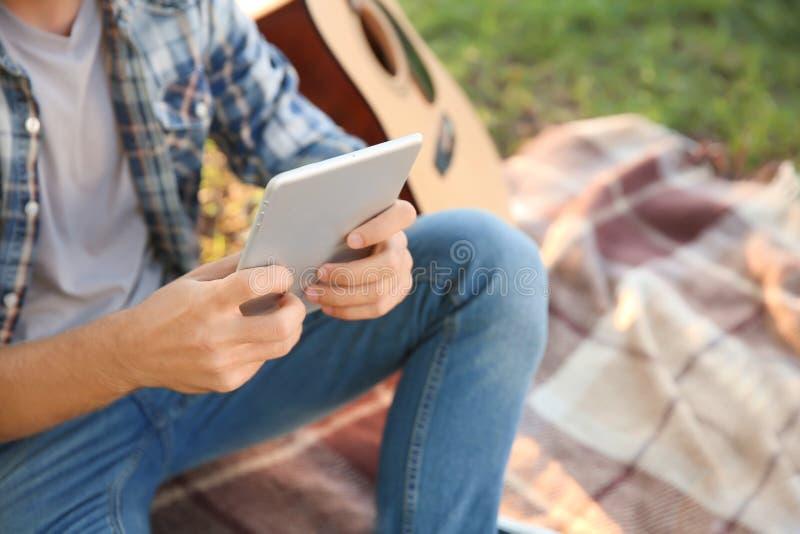 有基于格子花呢披肩的平板电脑的年轻人在公园 图库摄影