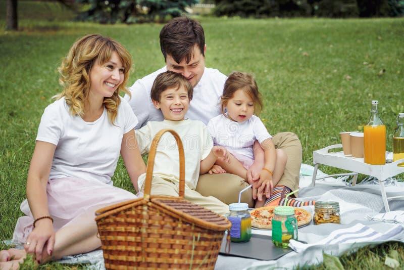 有基于草的孩子的幸福家庭在野餐期间 r 免版税库存照片