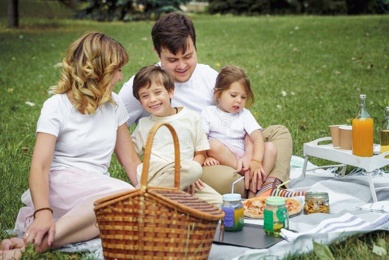 有基于草的孩子的幸福家庭在野餐期间 r 免版税库存图片