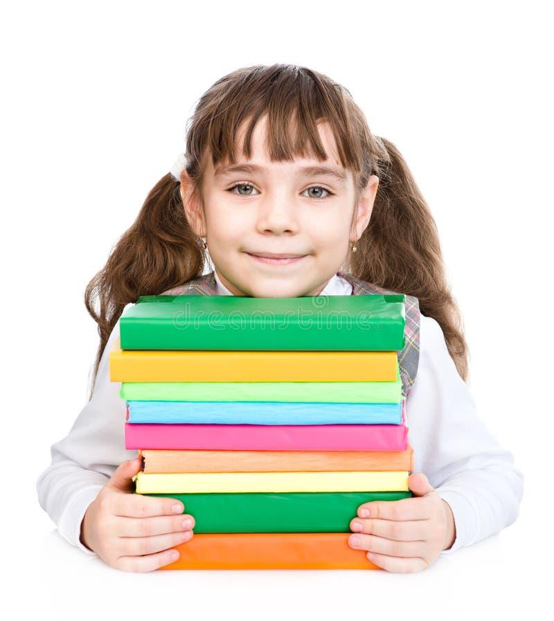 有堆书的小愉快的女孩 背景查出的白色 免版税库存图片