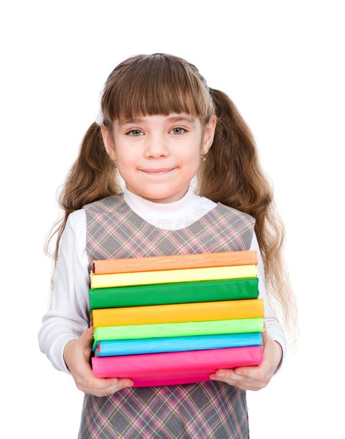 有堆书的小愉快的女孩 背景查出的白色 免版税库存照片