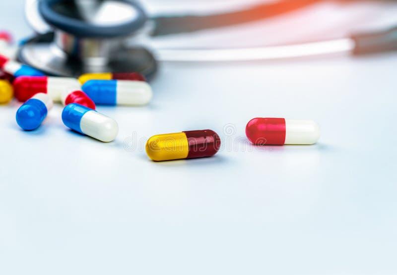 有堆的听诊器在白色桌上的五颜六色的抗药性胶囊药片 抗菌药物抗性和过度使用 医疗 免版税库存图片