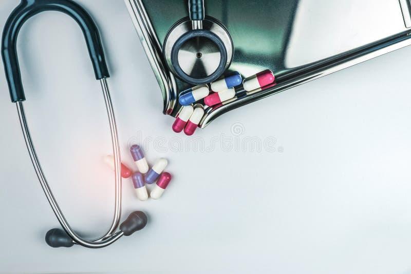 有堆的听诊器在白色桌上的抗药性胶囊药片在药物盘子附近 抗菌药物抗性和过度使用 免版税库存照片
