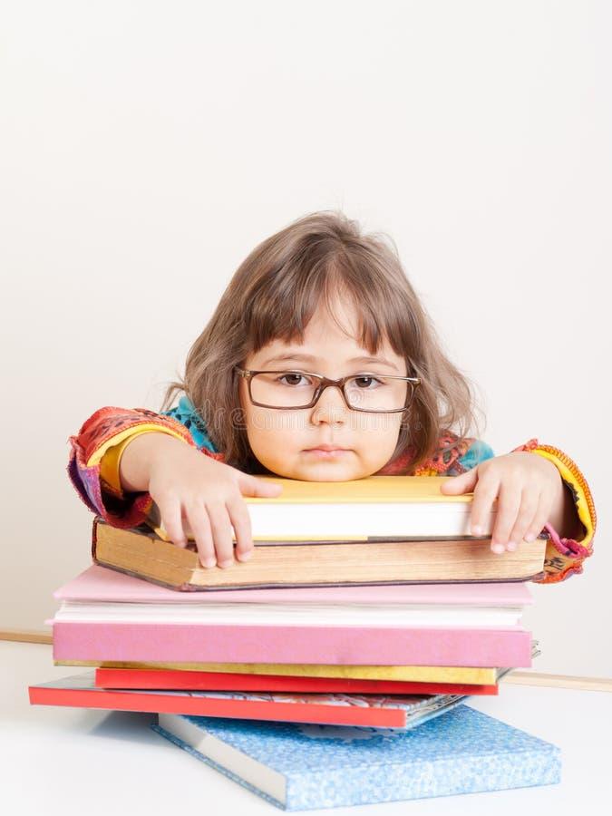 有堆的哀伤的疲乏的女孩书 免版税库存图片