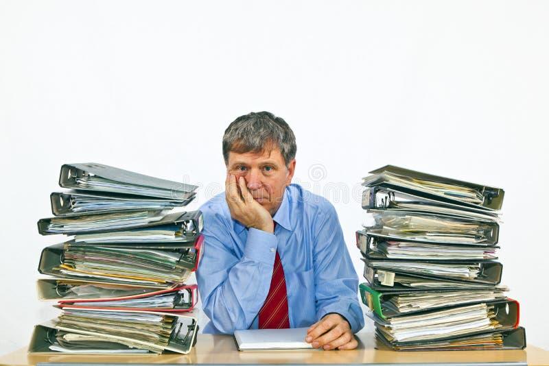 有堆的商人在他的书桌上的圆环包扎工具 免版税库存图片