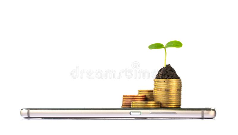 有堆的巧妙的电话硬币和幼木在上面 免版税库存图片