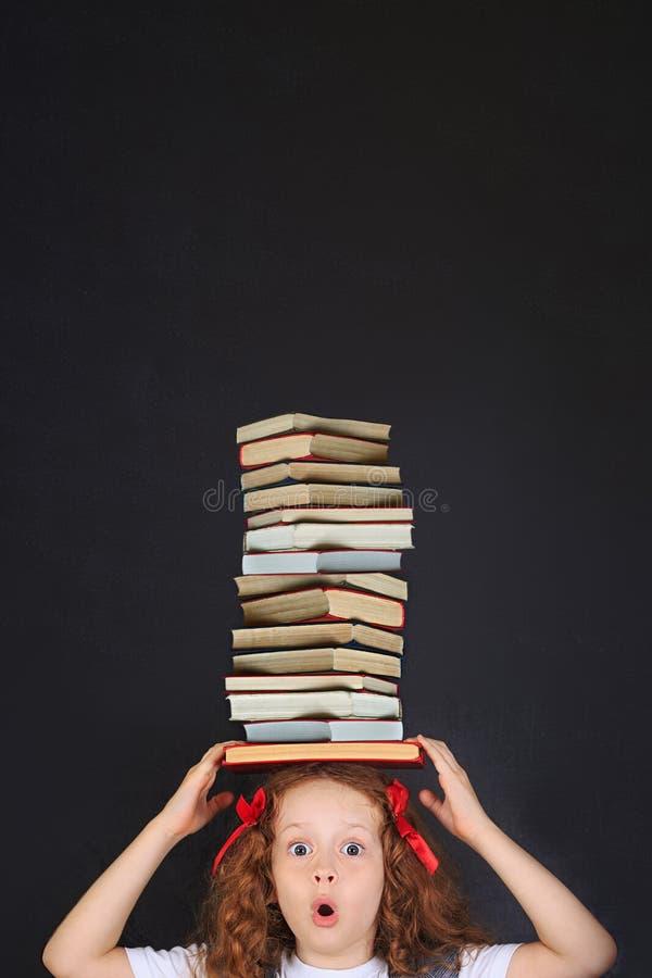 有堆的惊奇的学校女孩在她的头的书 免版税库存图片