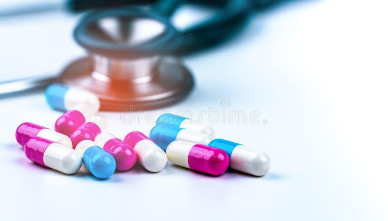 有堆的绿色听诊器在白色桌上的抗药性胶囊药片在药物盘子附近 抗菌药物抗性和过度使用 免版税库存照片