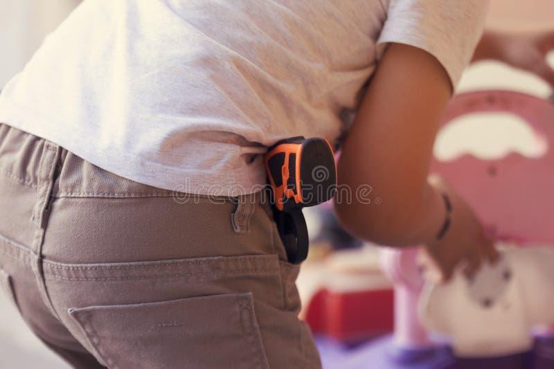 有塑料枪的小男孩在牛仔裤装在口袋里 有玩具使用在户外的手枪枪的愉快的男孩在夏日 免版税库存图片