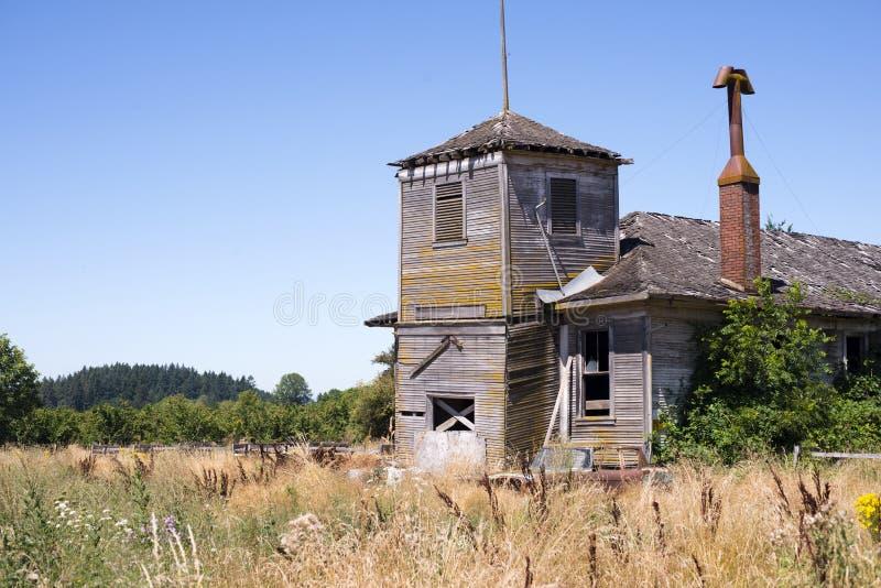 有塔和烟囱的老被放弃的木房子 免版税库存照片