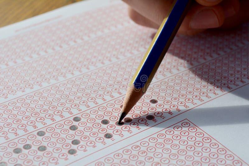 有填好在检查测试答案纸的铅笔的手答复 库存照片