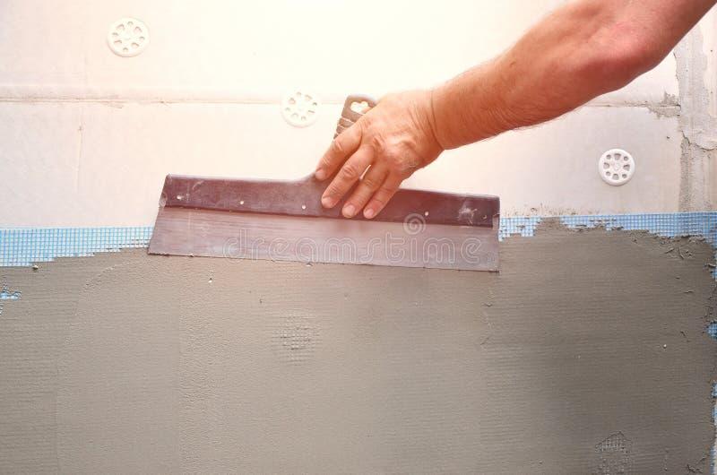 有墙壁的涂灰泥工具的一名老体力工人的手更新房子 更新室外墙壁和角落与的石膏工 库存图片