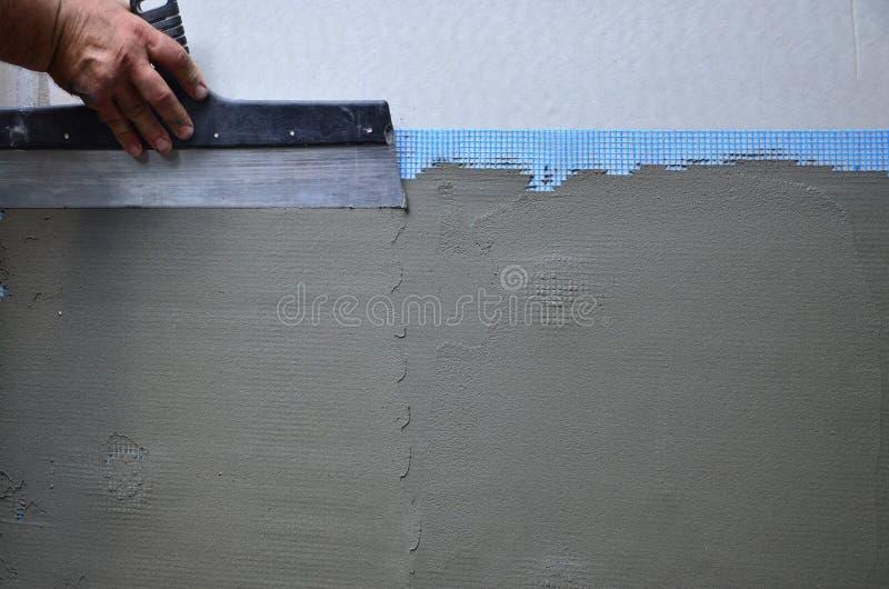 有墙壁的涂灰泥工具的一名老体力工人的手更新房子 库存照片