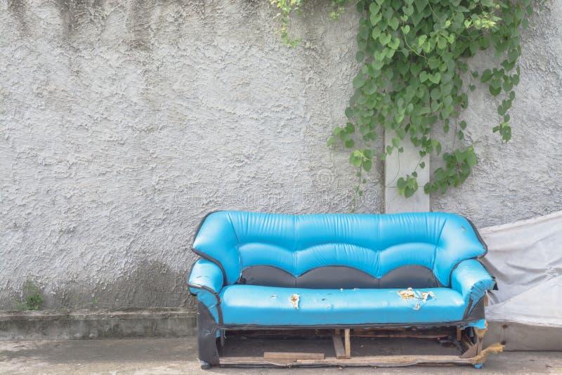 有墙壁的老沙发有藤垂悬 免版税库存照片
