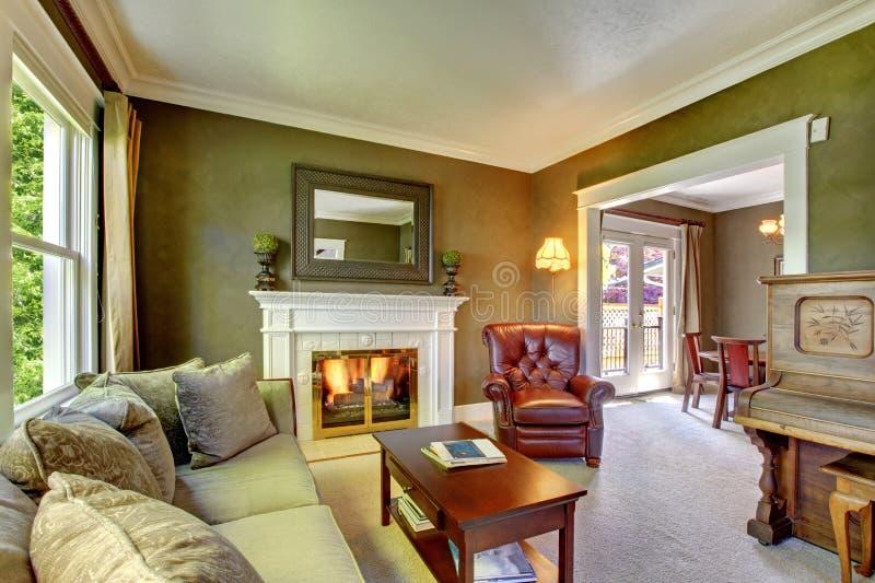 有壁炉和钢琴的典雅的经典绿色客厅。 库存图片