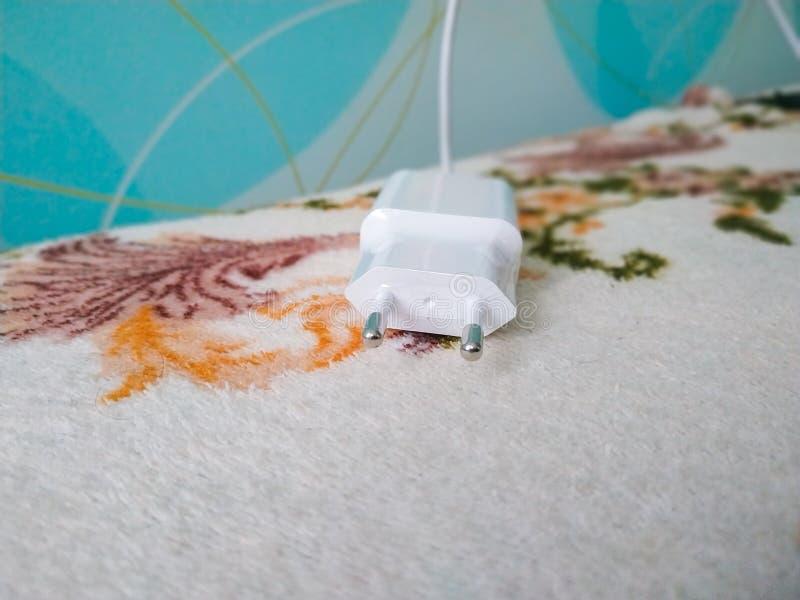 有壁装电源插座的流动手机充电器在卧室 免版税图库摄影