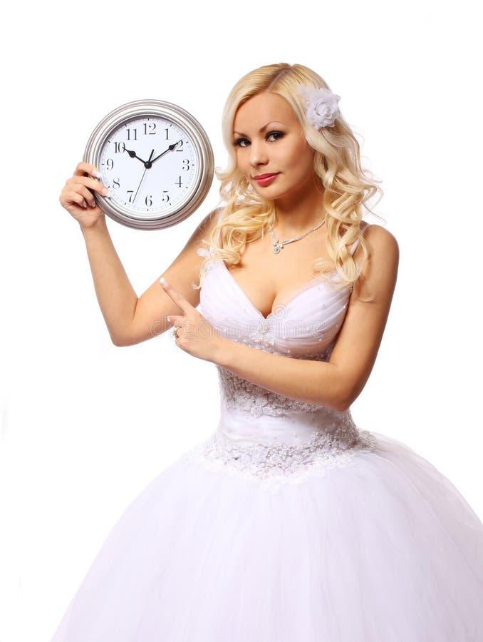 有壁钟的新娘。等待新郎的美丽的白肤金发的少妇被隔绝 库存图片