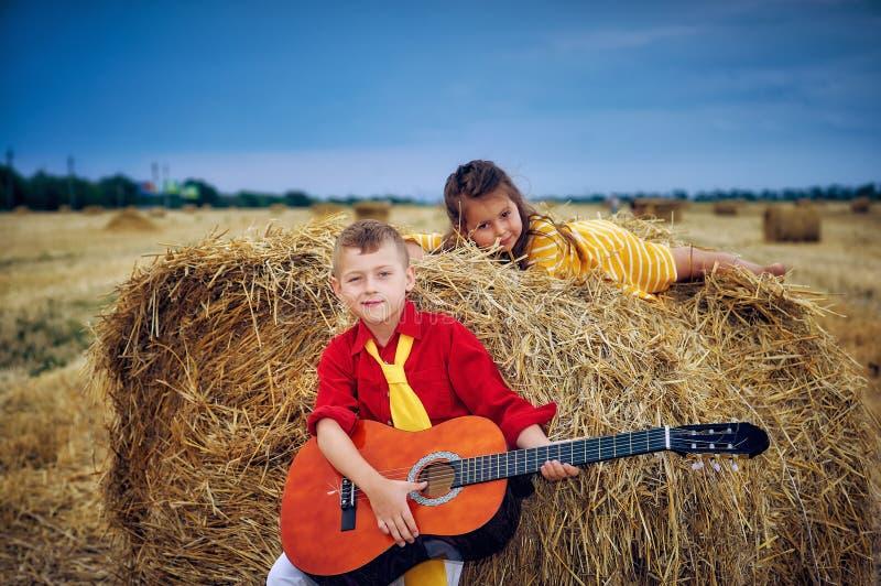 有声学吉他的男孩步行的在领域的一个夏天晚上 兄弟和姐妹户外 库存照片