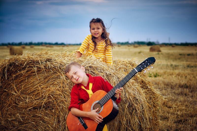 有声学吉他的男孩步行的在领域的一个夏天晚上 兄弟和姐妹户外 免版税库存图片
