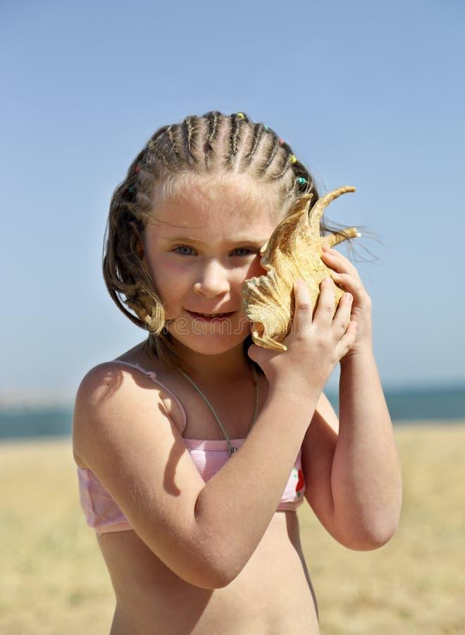 有壳的在海滩-葡萄酒减速火箭的样式小女孩 免版税库存图片