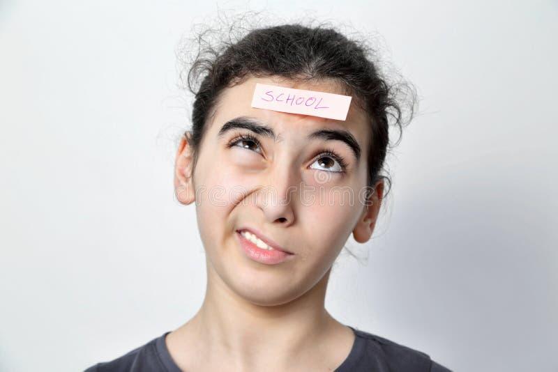 有备忘录岗位的女孩在她的前额 图库摄影