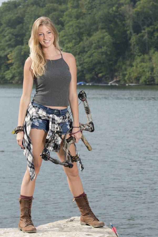 有复合弓的美丽的年轻白肤金发的女性射手 库存照片