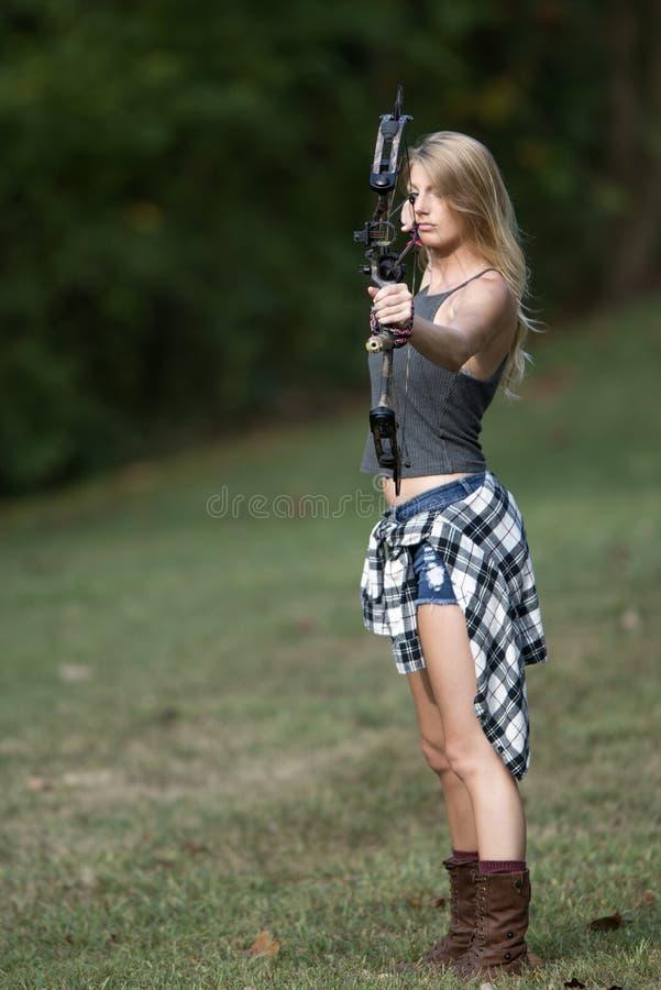 有复合弓的美丽的年轻白肤金发的女性射手 免版税库存图片
