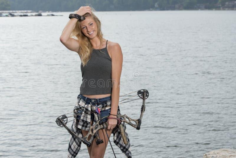 有复合弓的美丽的年轻白肤金发的女性射手 库存图片