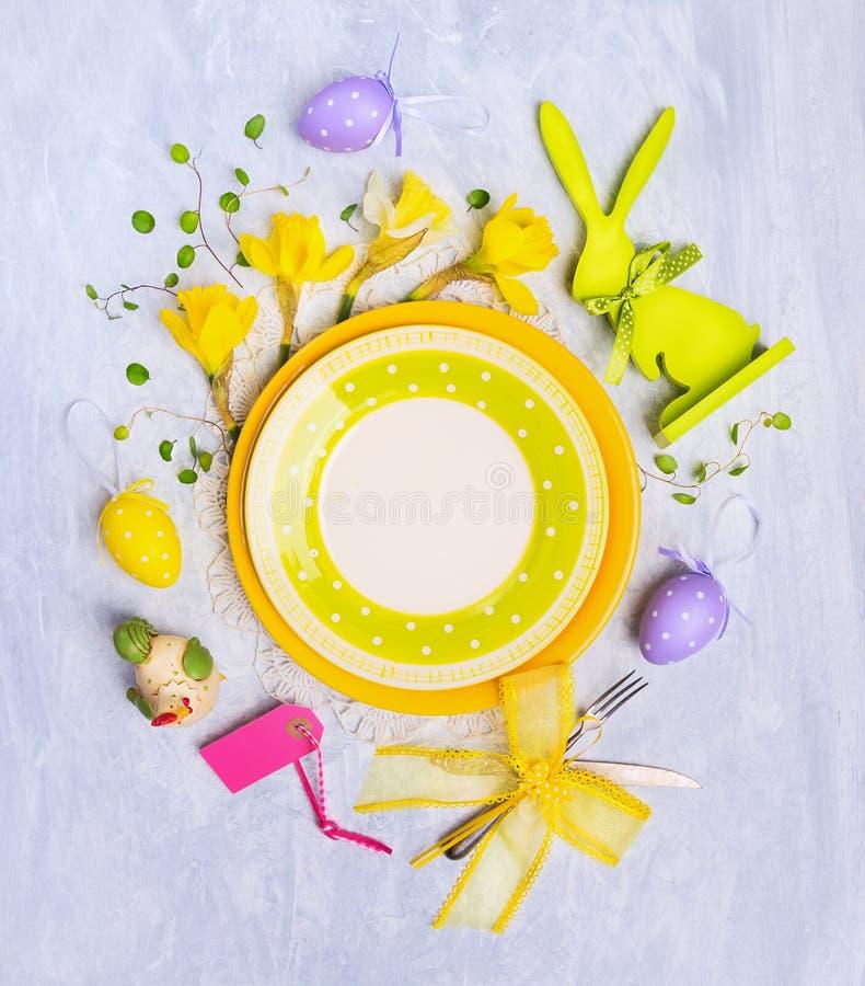 有复活节彩蛋装饰、标志和花的空的板材在灰色木背景,顶视图 免版税库存图片