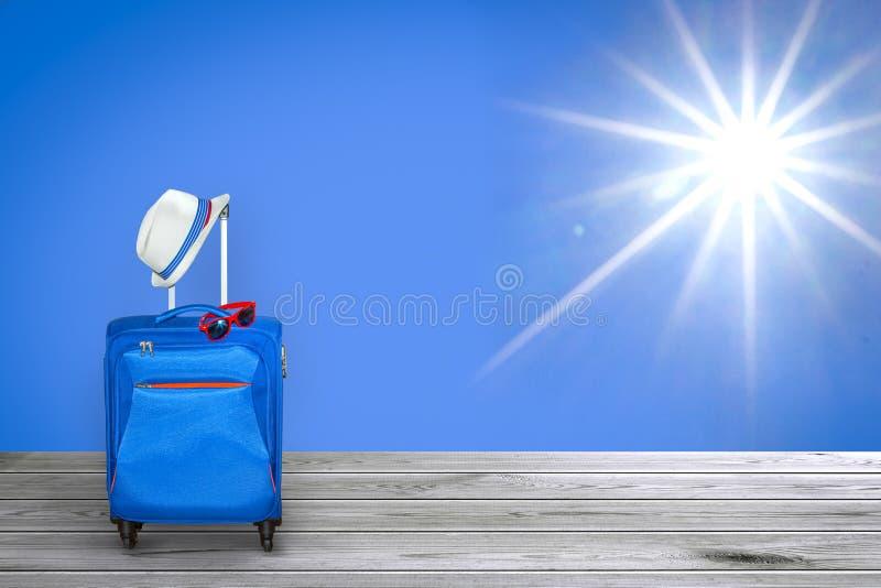 有夏天帽子和时兴的太阳镜的蓝色手提箱在与射线的光亮的公平的明亮的太阳在清楚的蓝天背景和wo 库存图片
