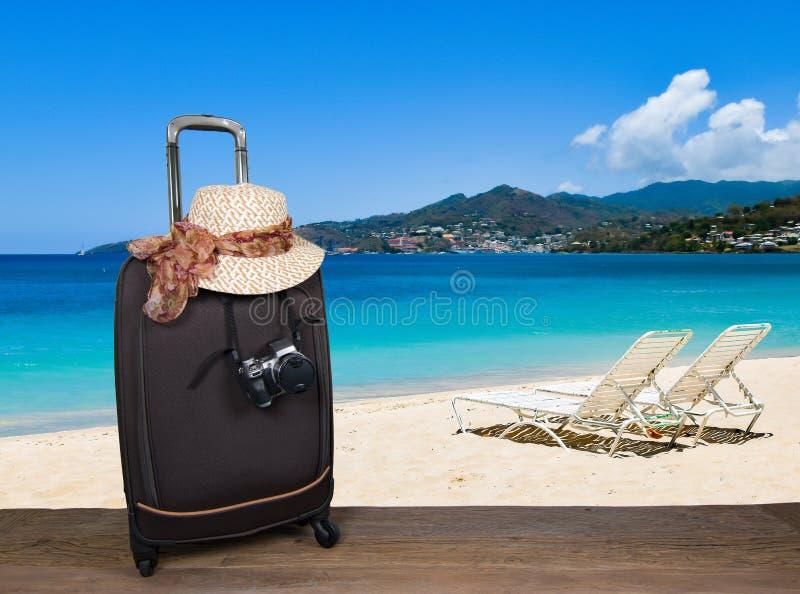 有夏天帽子的在热带海滩的手提箱和照相机 库存照片