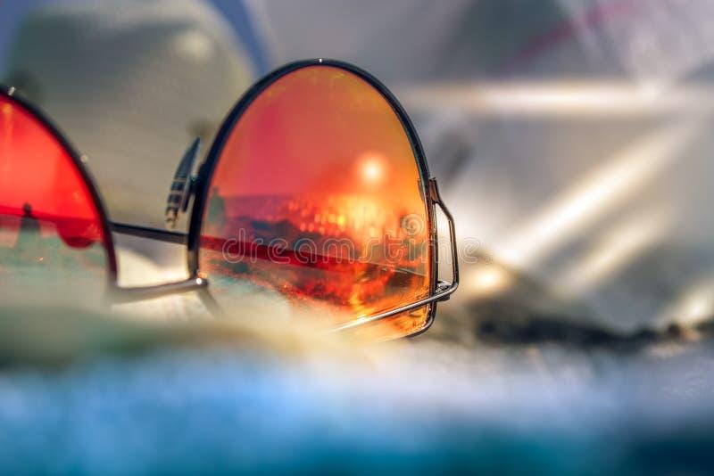 有夏天的反射的太阳镜靠岸与黑沙子、太阳和海 capri意大利 免版税库存图片