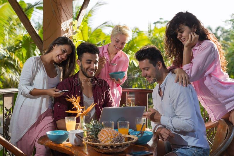有夏天的大阳台的人们早餐用途便携式计算机、妇女和人在自然的早晨吃谈话户外 免版税库存图片
