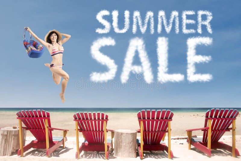 有夏天销售云彩的女孩在海岸 库存照片