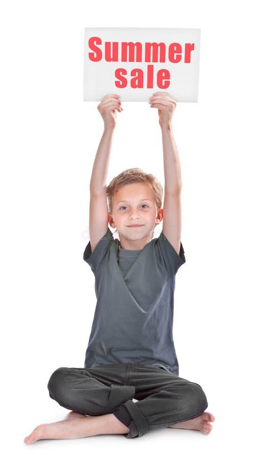 有夏天销售题字的男孩 免版税库存照片