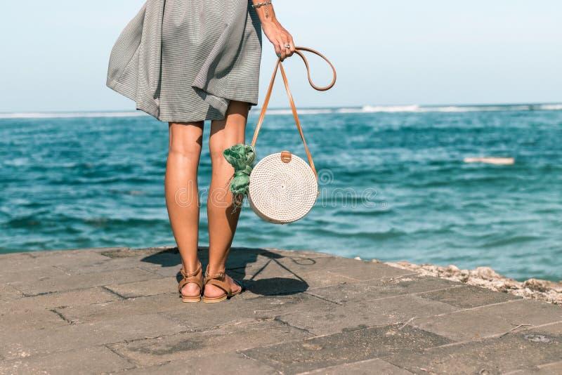 有外面时兴的时髦的白色藤条袋子和丝绸围巾的妇女 巴厘岛,印度尼西亚热带海岛  藤条 库存图片