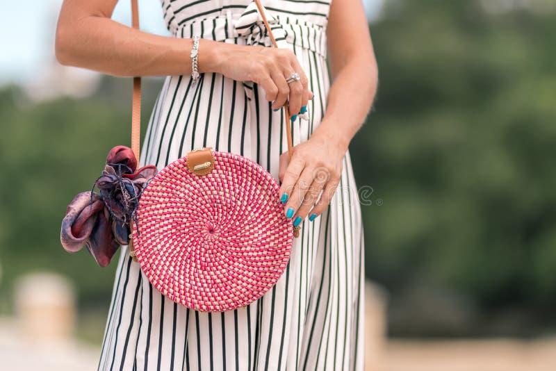 有外面时兴的时髦的红色藤条袋子和丝绸围巾的妇女 巴厘岛,印度尼西亚热带海岛  藤条提包 库存图片