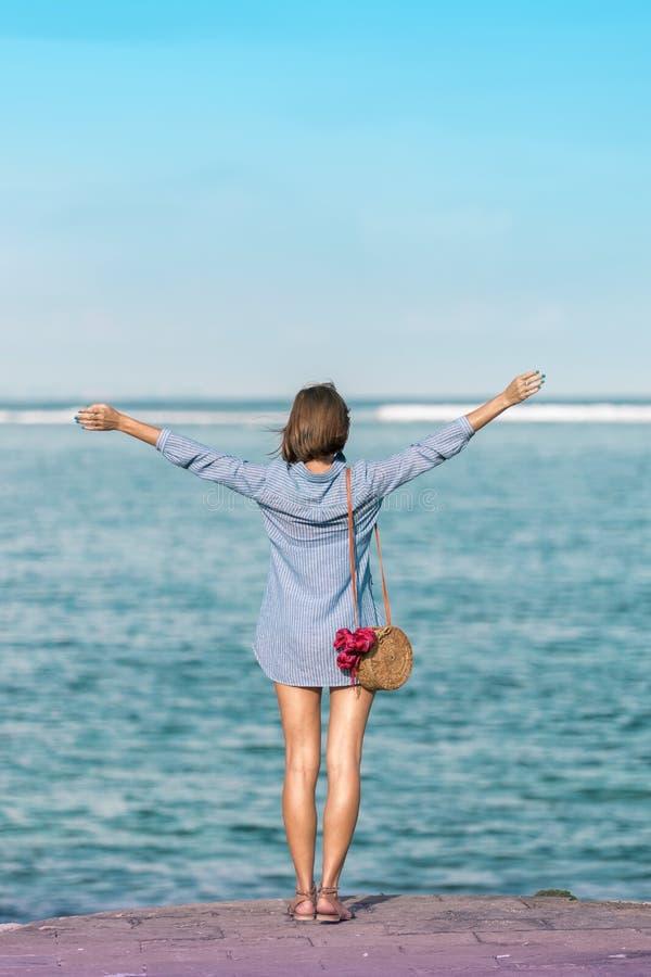 有外面时兴的时髦的藤条袋子和丝绸围巾的妇女 巴厘岛,印度尼西亚热带海岛  藤条提包和 免版税库存图片