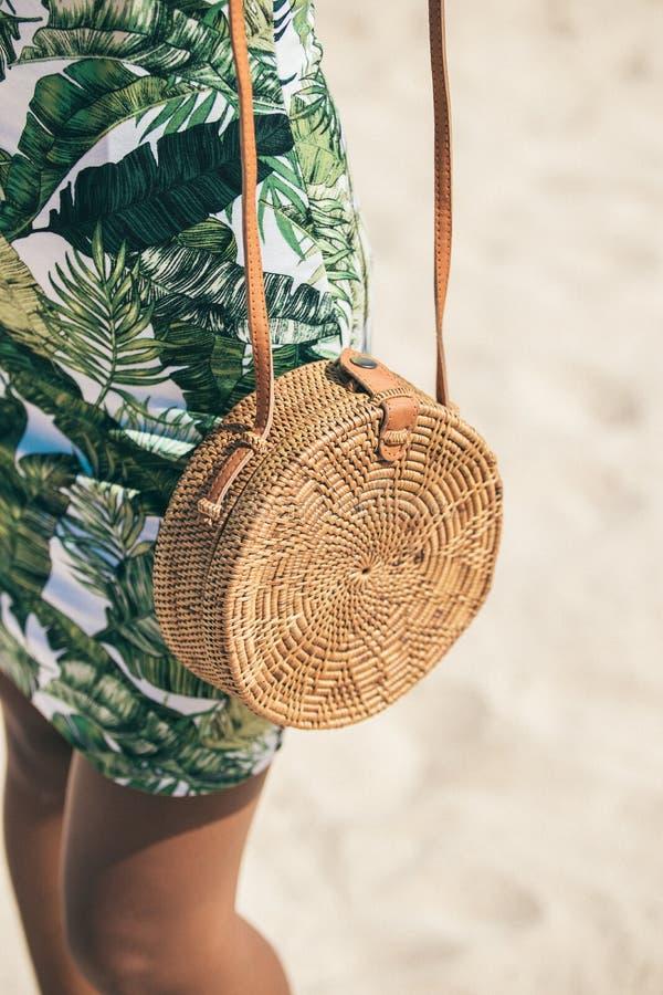 有外面时兴的时髦的藤条袋子和丝绸围巾的妇女 巴厘岛,印度尼西亚热带海岛  藤条提包和 库存图片