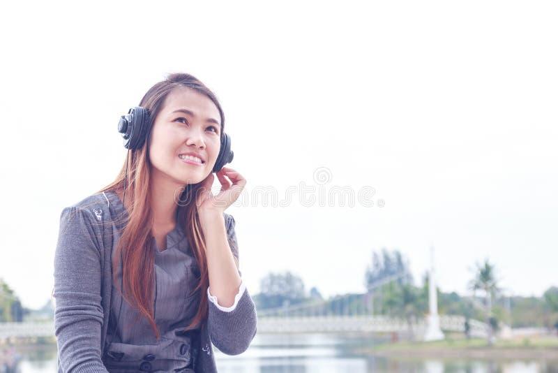 有外面耳机的少妇 库存图片