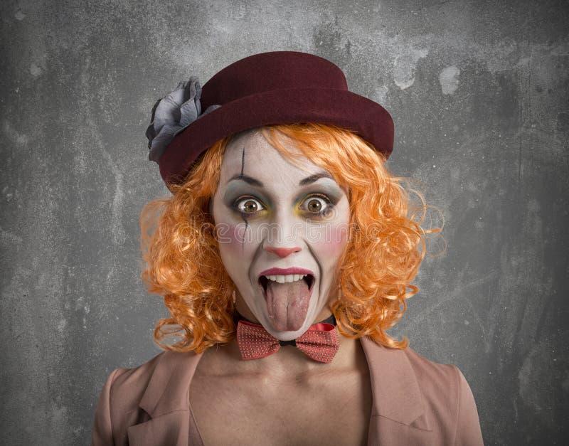 有外面舌头的滑稽的鬼脸小丑女孩女孩 免版税库存图片