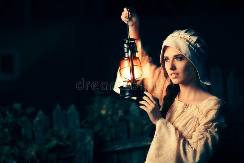 有外面葡萄酒灯笼的中世纪妇女在晚上 免版税库存图片
